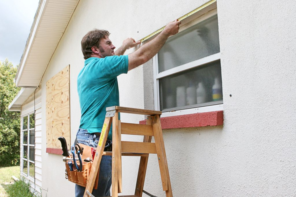 repair-man-preparing-windows-home-florida-hurricane-shelter-protection