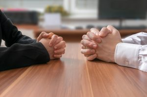 two-mens-arms-sitting-across-table-from-one-another-negotiating