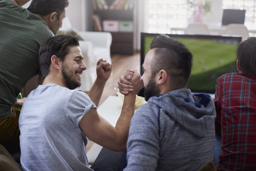 two-men-celebrating-in-man-cave-after-negotiating-with-insurance-company