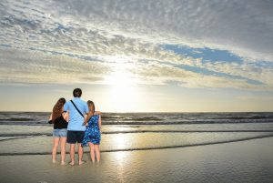 Family of three - mother, father, and young daughter - on the beach watching the sunrise.